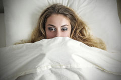 Hiding under the sheets Stock Image