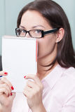 Hiding woman. Portrait of a playful woman hiding behind the notebook royalty free stock photos