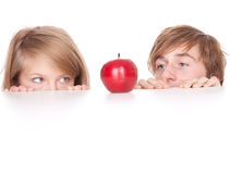 Hiding young couple. Young couple hiding behind and peeking behind the white table Royalty Free Stock Image