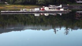 Hidroavión del hidroavión en el agua del estacionamiento en costa del fondo en Alaska almacen de video