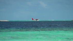 Hidroavión en el fondo del paisaje marino y el cielo de Maldivas metrajes