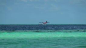 Hidroavión en superficie y horizonte del agua del fondo en Maldivas metrajes