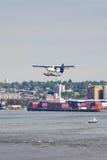 Hidroavión que se prepara para el aterrizaje del agua en el puerto del envase Imagen de archivo