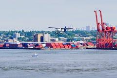 Hidroavión y envases apilados en puerto Foto de archivo libre de regalías