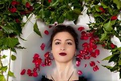 Hiedra de las hojas de las rosas rojas del baño de agua de la leche de la muchacha fotos de archivo
