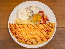 Hiele el crepé del creame con la salsa y el plátano de la fresa Foto de archivo libre de regalías