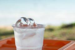 Hiele en un vidrio de agua y de fondo natural Imagenes de archivo