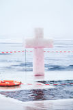 Hiele la cruz y agujeréela en la charca del invierno en epifanía Foto de archivo libre de regalías