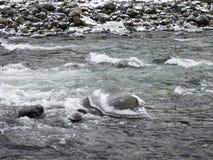Hiele las rocas cubiertas en Sandy River con los casquetes glaciares de la seta Foto de archivo libre de regalías