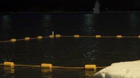 Hiele los flotadores blancos protegidos agujero en el río en la noche metrajes