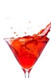 Hiele salpicar en un martini rojo Foto de archivo
