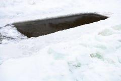 Hielo-agujero con agua congelada en bloques de la charca y de hielo Imagen de archivo libre de regalías