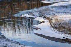 Hielo del río con reflexiones del árbol Foto de archivo