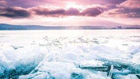 Hielo en una superficie congelada con el cielo nublado púrpura impresionante en el fondo foto de archivo