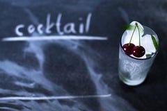Hielo natural en un vidrio con las cerezas en un fondo negro Imágenes de archivo libres de regalías