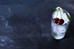 Hielo natural en un vidrio con las cerezas en un fondo negro Imagen de archivo