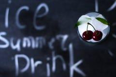 Hielo natural en un vidrio con las cerezas en un fondo negro Fotografía de archivo