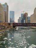 Hielo que flota en el río Chicago mientras que el tren del EL cruza encima en la calle de Wells fotos de archivo libres de regalías