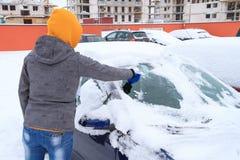 Hielo que raspa de la mujer de la ventanilla del coche Imagen de archivo