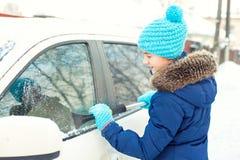 Hielo que raspa del adolescente joven en la ventanilla del coche de la nieve del invierno Foto de archivo libre de regalías