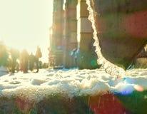 Hielo y nieve que derriten, agua que corre abajo del tubo en el día de primavera soleado caliente Foto de archivo