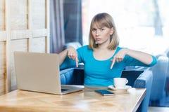 Hier en nu! Het portret van boze ongelukkige jonge onderneemster in blauwe blouse zit in koffie en hebbend slechte stemming tonen royalty-vrije stock fotografie
