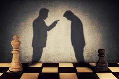 Hierarchical levels. Chess pawn and king standing in front one another with their shadow transform into businessman silhouettes. Business hierarchy Royalty Free Stock Photography