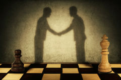 Hierarchical peace. Chess pawn and king standing in front one another with their shadow transform into businessman giving handshake. Business hierarchy levels Royalty Free Stock Photography