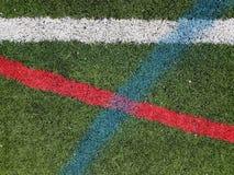 Hierba artificial con las líneas blancas, rojas, y azules imagenes de archivo