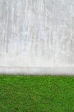 Hierba artificial en una pared del cemento Foto de archivo