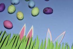 Hierba con los oídos de conejo y los huevos de caramelo en azul foto de archivo