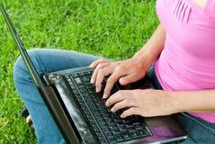 Hierba de la computadora portátil de la mujer Imágenes de archivo libres de regalías