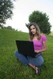 Hierba de la computadora portátil de la mujer Fotografía de archivo libre de regalías