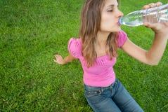 Hierba del agua de la bebida de la mujer Imagen de archivo