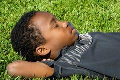 Hierba el dormir del muchacho Fotografía de archivo
