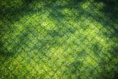 Hierba falsa verde con la sombra de la cerca para el parque de la seguridad Foto de archivo