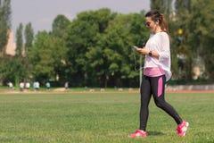 Hierba que camina de la muchacha atlética joven Imagenes de archivo