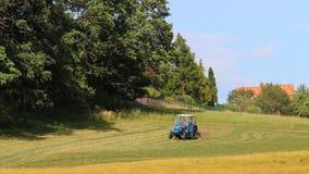 Hierba seca de la vuelta azul del tractor, heno cerca del bosque, escena rural, paisaje checo almacen de metraje de vídeo