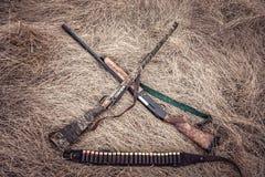 Hierba seca de las escopetas de la caza en pajar como fondo de la caza en estilo del oeste salvaje Foto de archivo libre de regalías