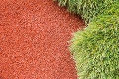 Hierba verde artificial con el fondo rojo marrón Fotografía de archivo