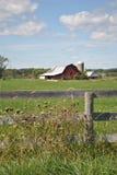 Hierba verde con la cerca y el granero de madera Imagen de archivo libre de regalías