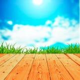 Hierba verde de la primavera fresca con el cielo azul y el piso de madera Imagenes de archivo