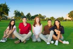Hierba verde de la sentada feliz de la gente del grupo de los amigos Imagen de archivo libre de regalías