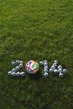 Hierba verde de los balones de fútbol de los equipos del fútbol 2014 Fotos de archivo
