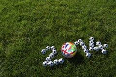 Hierba verde de los balones de fútbol de los equipos del fútbol 2014 Fotos de archivo libres de regalías