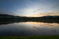 Hierba verde, lago, montañas y bosque durante salida del sol con la luz oscuro Fotos de archivo libres de regalías
