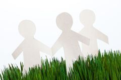 Hierba verde y hombres de cadena de papel Imagenes de archivo