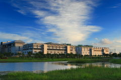 Hierba verde y lago con la fábrica de alta tecnología fotos de archivo