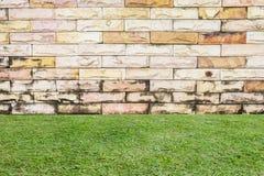 Hierba y un fondo de la pared de ladrillo Imagen de archivo libre de regalías