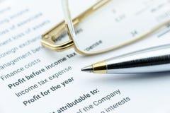 Hierbas azules del bolígrafo y del ojo en el informe financiero de una compañía, en la parte de beneficio y de renta neta foto de archivo libre de regalías